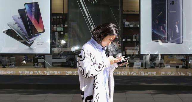 In this Tuesday, Oct. 17, 2017 file photo, a woman walks by posters adverting smartphones at a mobile phone shop in Seoul, South Korea. (AP Photo)