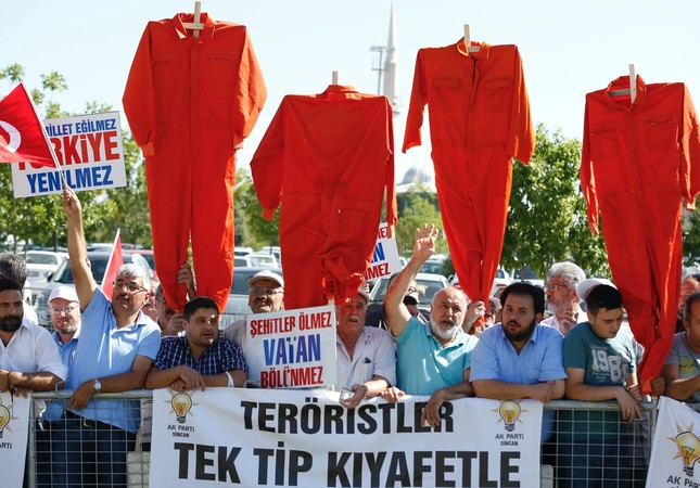 Protesters brandish orange jumpsuits as defendants in a major coup trial in Ankara are being brought to the court for trial on Aug. 1.