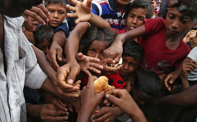 Myanmar's Muslim Rohingya ethnic minority children stretch their hands out to receive food distributed by locals at the Kutupalong makeshift refugee camp in Cox's Bazar, Bangladesh, Wednesday, Aug. 30, 2017. (AP Photo)
