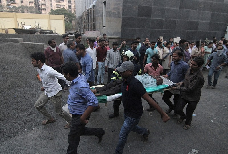 People carry a man to a safer place after he was evacuated from a government hospital due to fire, on the suburbs of Mumbai, India, Dec. 17, 2018. (Reuters Photo)