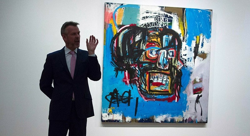 This file photo taken on May 5, 2017 shows a Sotheby's official speaking about ,Untitled,, a 1982 painting by Jean-Michel Basquiat during a media preview at Sotheby's in New York. (AFP Photo)