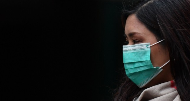 A pedestrian wears a surgical mask in London's China Town on January 24, 2020. AFP Photo