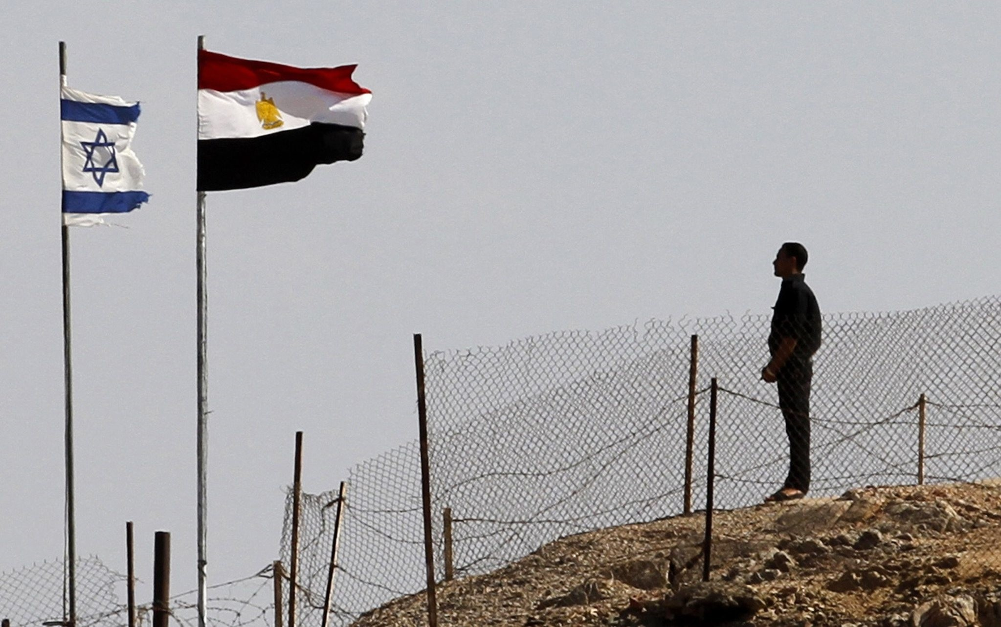 An Egyptian soldier stands near the Egyptian national flag and the Israeli flag at the Taba crossing between Egypt and Israel, about 430 km (256 miles) northeast of Cairo, October 26, 2011. (Reuters Photo)