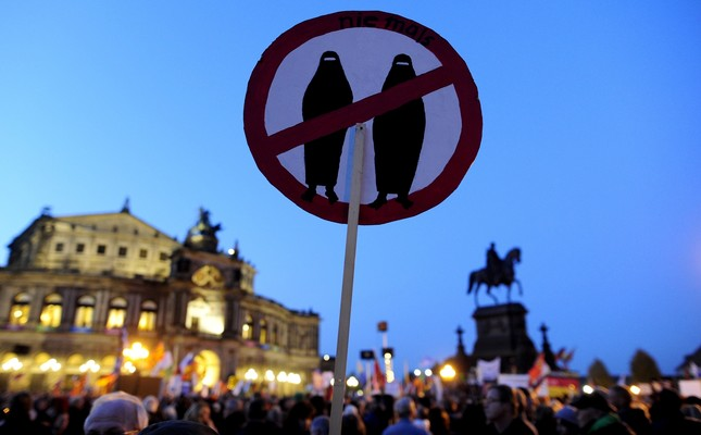 A supporter of the Pegida movement holds a poster featuring a crossed sign on veiled  women at a protest rally in Germany.