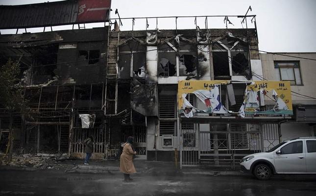 A pedestrian walks past buildings that were burned down during protests in Karaj, Iran, Nov. 18, 2019. (AP Photo)
