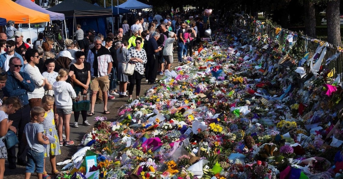Floral tributes to those who were gunned down at the two mosques are seen against a wall bordering the Botanical Gardens in Christchurch, March 19, 2019.
