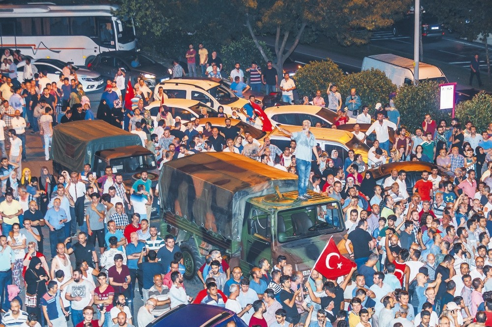 People surround military trucks of putschist troops on July 15, 2016, outside AK Party offices in Istanbul during the coup attempt. Fifteen putschists involved in the takeover of the offices were sentenced to life yesterday.