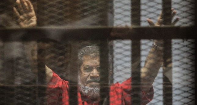 Mohamed Morsi gestures during a trial session on charges of espionage in Cairo, Egypt, 18 June 2016. (EPA)