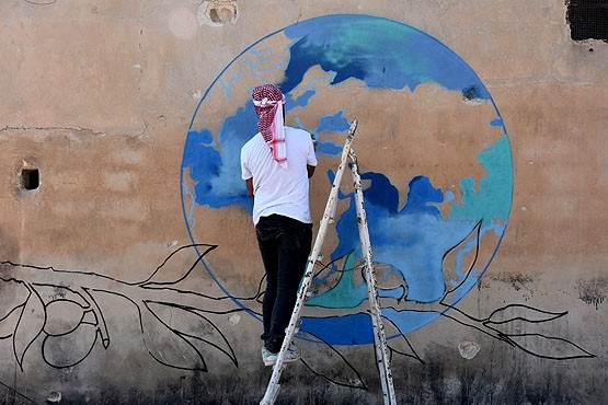 ,The world map above a bloody olive branch can best illustrate the tragedy in Syria,, says graffiti artist, Mr. Hure.