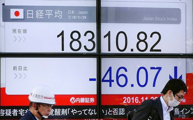 Men stand near an electronic stock board showing Japan's Nikkei 225 index at a securities firm in Tokyo. Asian stocks were mixed as concerns over an OPEC oil production cut and Italy's constitutional referendum cast a pall on the markets. (AP Photo)