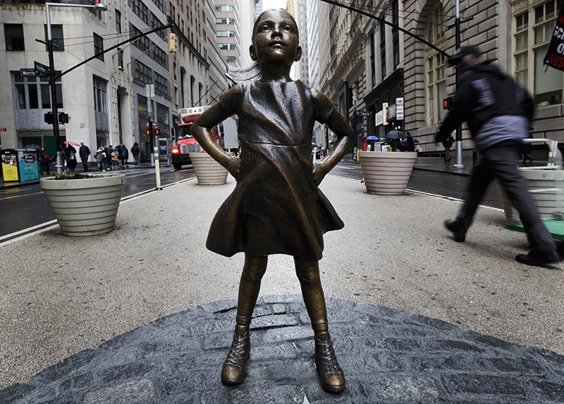 People are seen around a sculpture titled 'The Fearless Girl' by artist Kristen Visbal facing the famous sculpture of the charging bull in Lower Manhattan to promote the idea of women in leadership positions in New York, 07 March 2017. (EPA Photo)