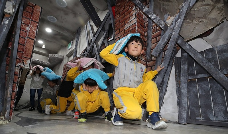 Children participate in a training program in Seoul, South Korea on Nov. 17 2017, that teaches them how to take shelter from an earthquake. (EPA Photo)