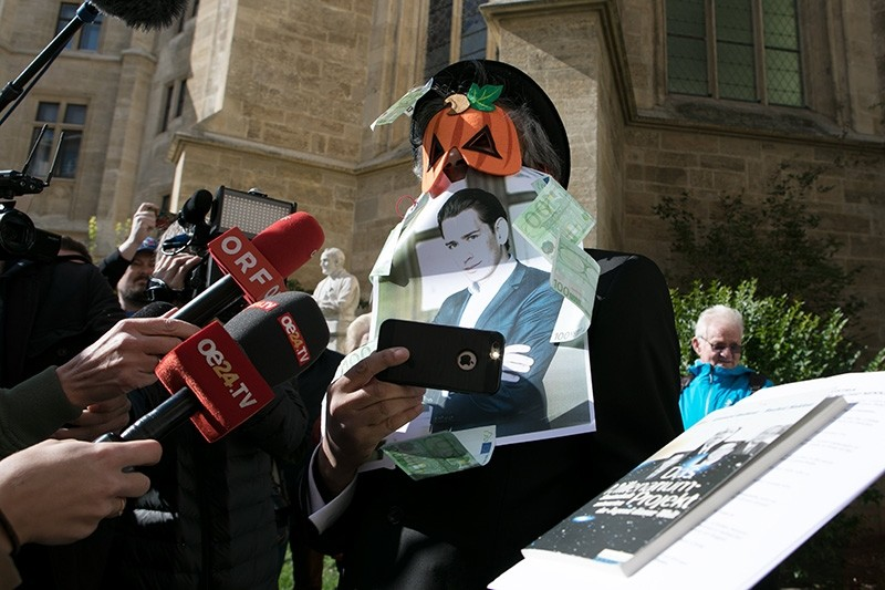 French-Algerian businessman Rachid Nekkaz, covering his face with a picture of Austrian Foreign Minister Sebastian Kurz and bank notes protests against a face van ban in Vienna, Austria, 09 October 2017. (EPA Photo)