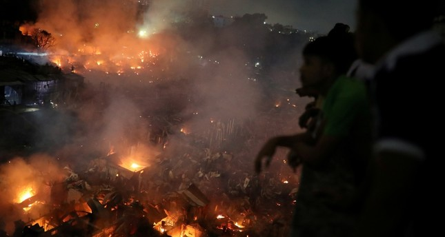 People gather at a rooftop to watch the fire that broke out at a slum in Dhaka, Bangladesh, August 16, 2019. Reuters Photo