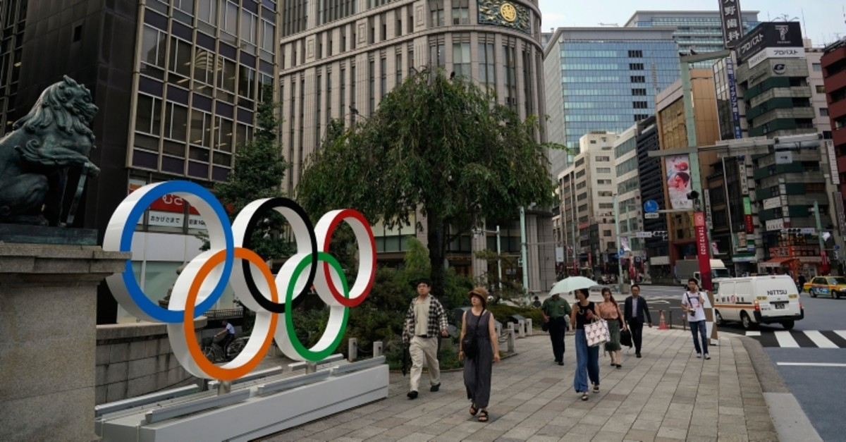In this Monday, Aug. 19, 2019, photo, people walk past the Olympic rings in Tokyo. (AP Photo)