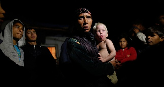 Bulgarian Roma woman holds her son as she speaks to media outside her house in the town of Nikolaevo, some 280 km (173 miles) east of Sofia, Bulgaria, Oct. 24, 2013. (Reuters Photo)