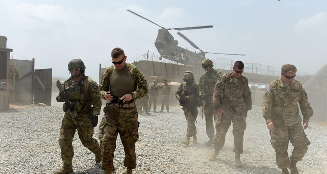 This Aug. 13, 2015 shows U.S. army soldiers walk as a NATO helicopter flies overhead at coalition force Forward Operating Base (FOB) Connelly in the Khogyani district in the eastern province of Nangarhar, Afghanistan. (AFP Photo)