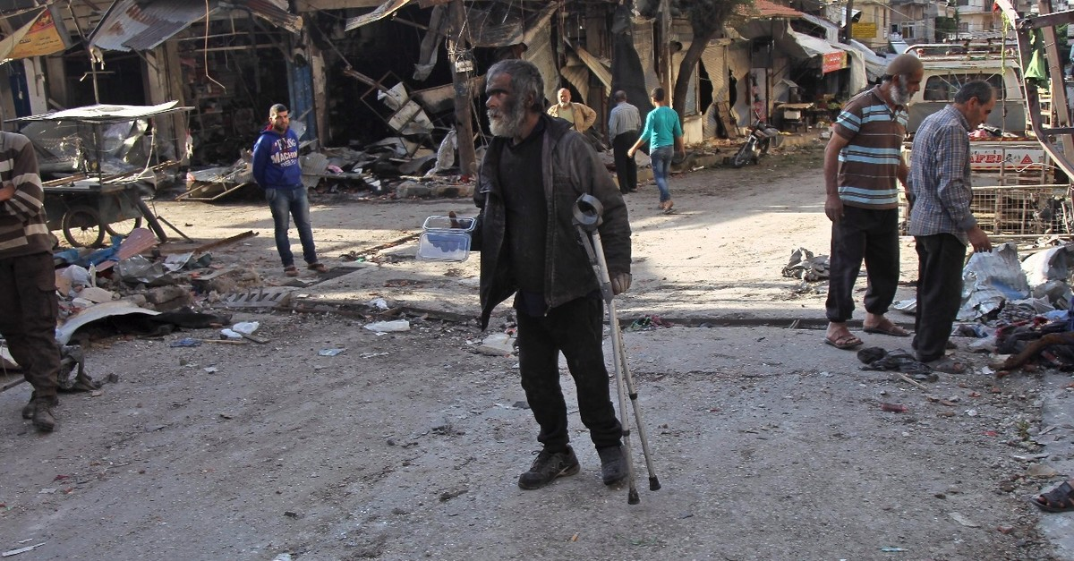 A Syrian man whose shop was destroyed in a regime aerial bombardment the previous day walks around the area in Idlib, May 15, 2019.