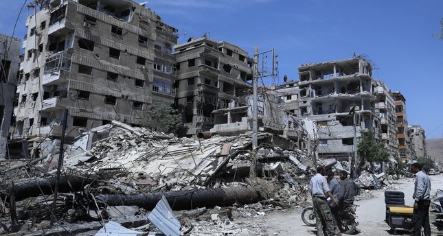 In this April 16, 2018, file photo, people stand in front of damaged buildings, in the town of Douma, near Damascus, Syria. (AP Photo)