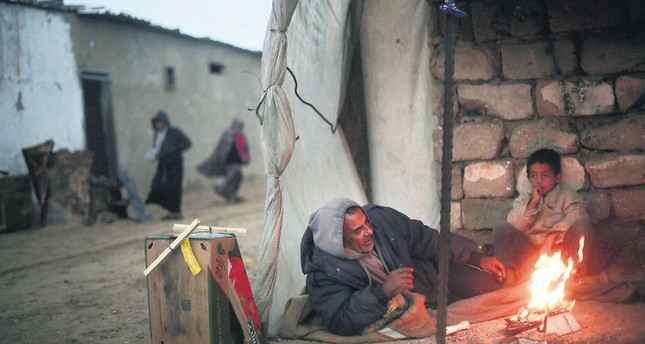A Palestinian man and his son warm themselves during cold, rainy weather in a slum on the outskirts of the Khan Younis refugee camp, southern Gaza Strip, Jan. 5.