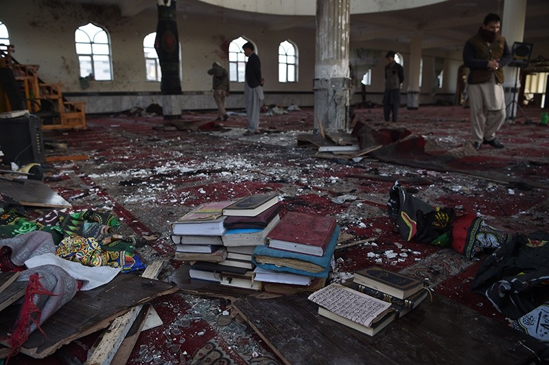 Afghan residents look inside the Imam Zaman Shiite mosque which was a the site of a suicide attack during evening prayers, in Kabul on October 21, 2017. (AFP Photo)