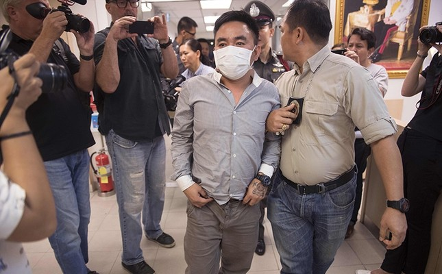 Boonchai Bach (C), 40, a Vietnamese national with Thai citizenship and alleged kingpin in Asia's illegal trade in endangered species, is escorted past journalists as he is processed at a police station in Bangkok on January 20, 2018. (AFP Photo)