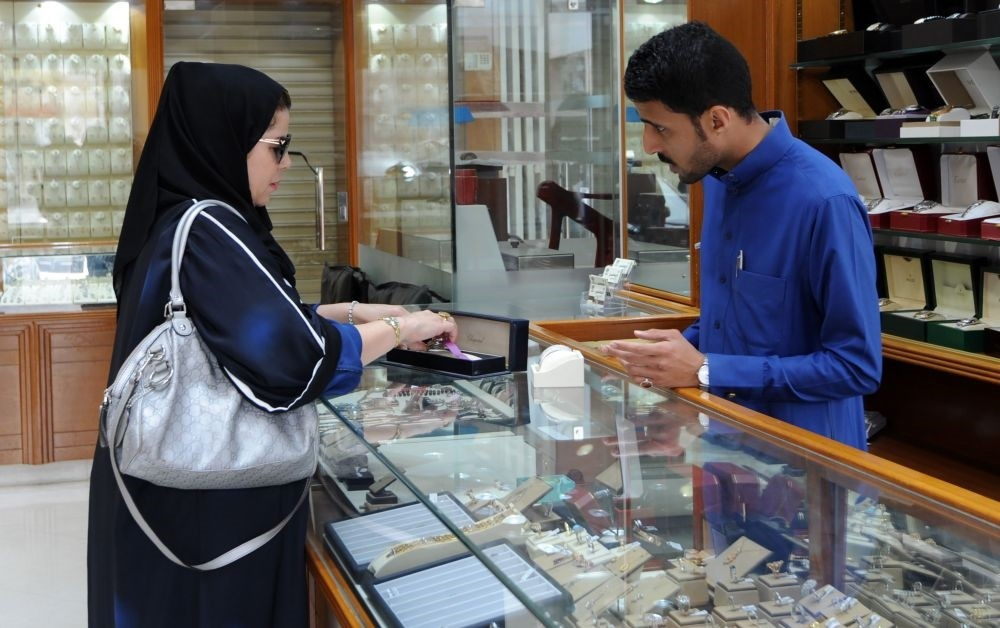 A Saudi jeweler attends to a client in a shop in the Tiba gold market, Riyadh.