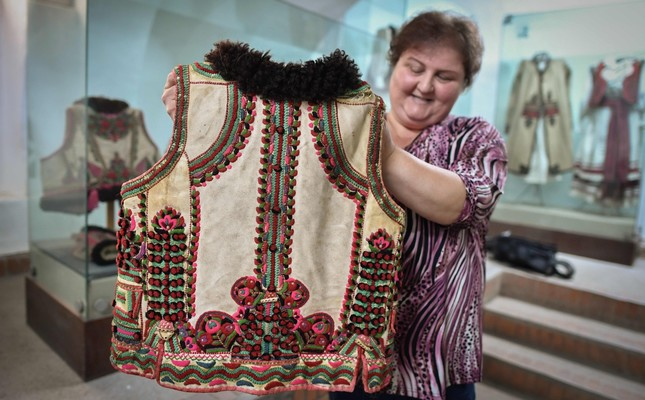 A woman working at the local museum shows a 100 year-old traditional outfit from the Bihor northwestern region of Romania in Beius, July 17.