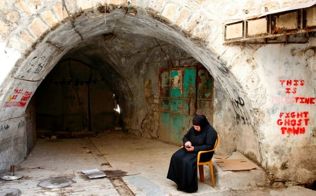 A Palestinian woman sits in the old city of the West Bank city of Hebron on May 8.