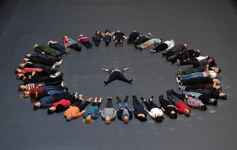 Cuban artist and activist Tania Bruguera (C) lies with volunteers on her installation during its unveiling in the Turbine Hall at Tate Modern in London, Britain, October 1, 2018. (EPA Photo)