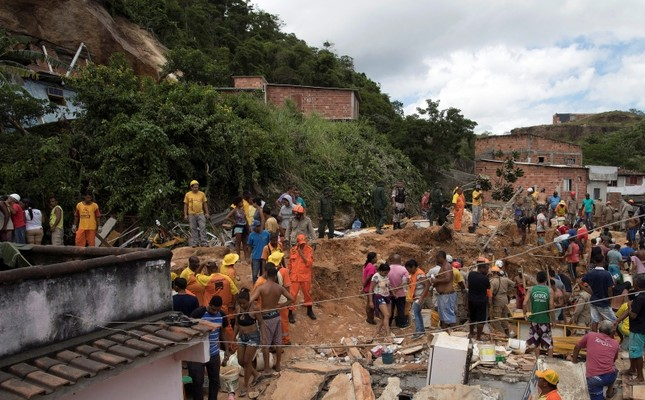 Residents, volunteers and firefighters work over the debris after a mudslide in Boa Esperanca or Good Hope shantytown in Niteroi, Brazil, Saturday, Nov. 10, 2018. (AP Photo)