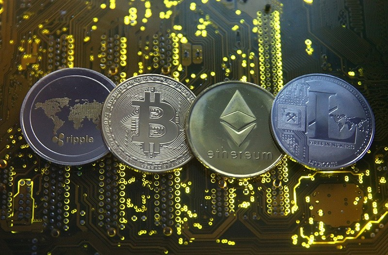 Representations of the Ripple, Bitcoin, Etherum and Litecoin virtual currencies are seen on a PC motherboard in this illustration picture, February 14, 2018. (Reuters Photo)