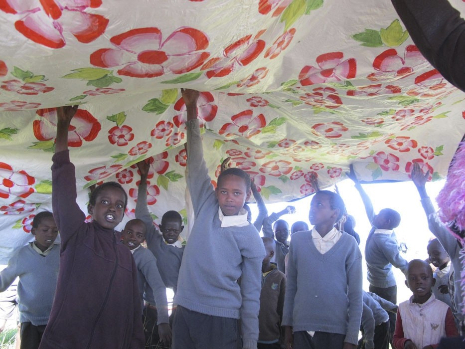 Local African children holding up a painted rain-chute.