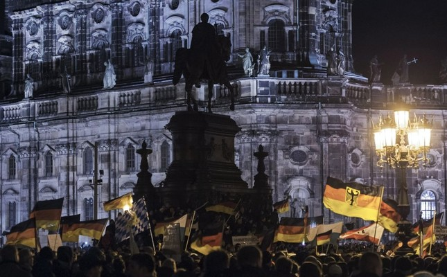 Far-right protesters holding German flags participate in a rally against Islam, in front of the bronze equestrian statue of King John of Saxony, Dresden, Dec. 22, 2014.