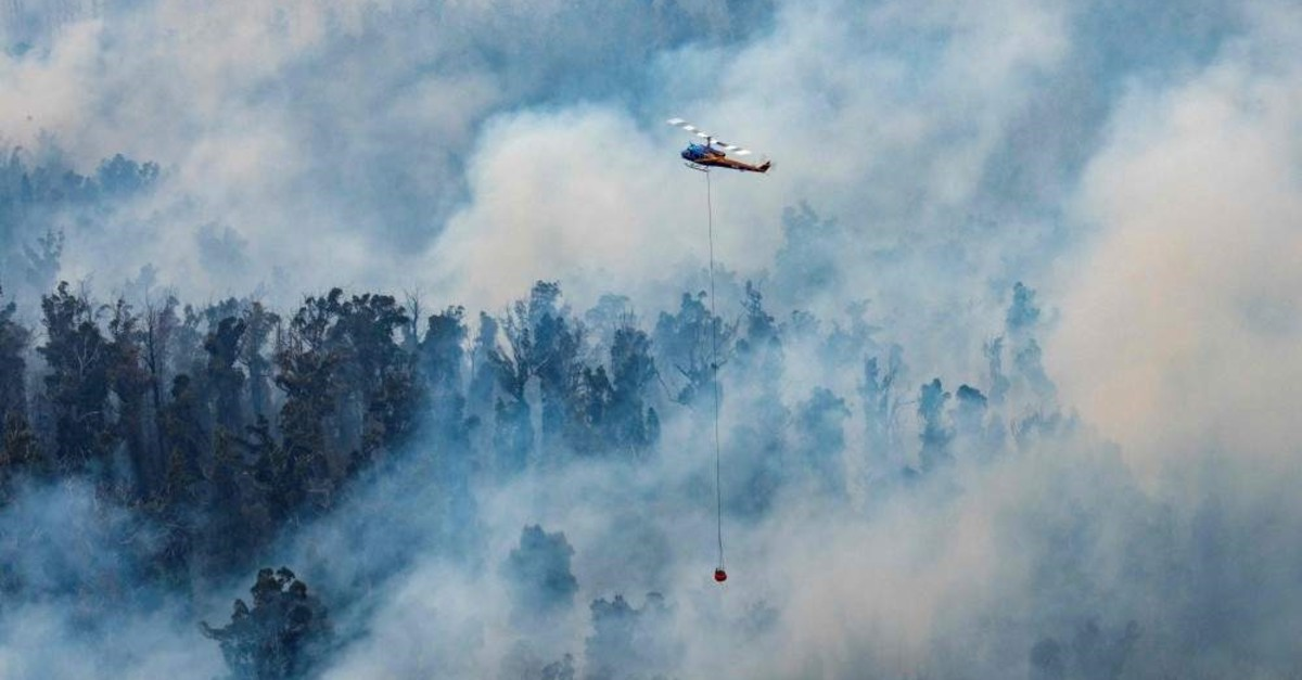 This Dec. 29, 2019, handout photo shows a helicopter dumping water on a fire in Victoria's East Gippsland region. (Victoria's Department of Environment, Land, Water and Planning via AFP)