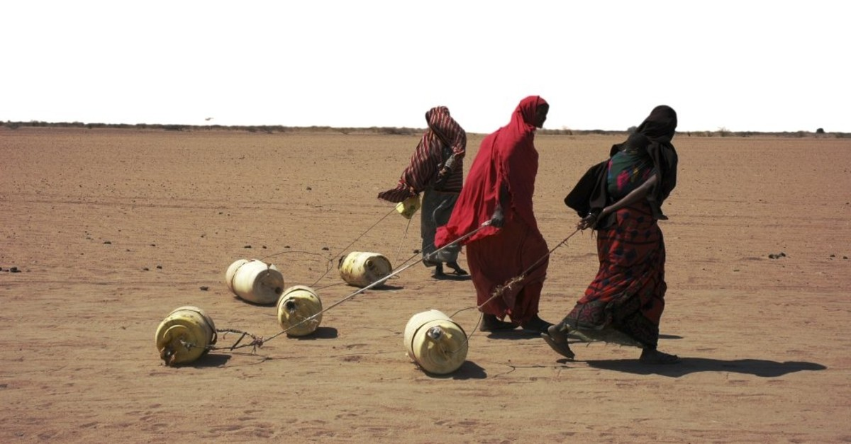 Drought-hit women dragging jerry cans to their homes in Kenya.