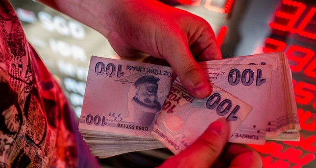 This Aug. 8, 2018 photo shows a money changer counting Turkish lira banknotes at a currency exchange office in Istanbul. (AFP Photo)