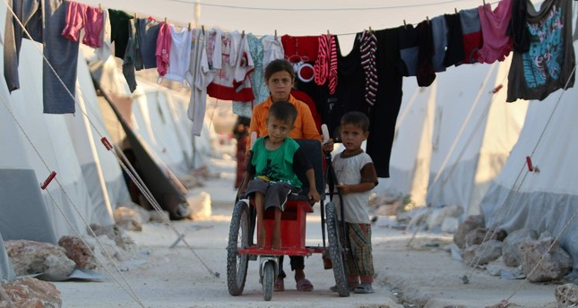 Syrian refugee children push a disabled boy in a makeshift wheelchair at a camp for displaced people in northern Idlib province, Aug. 29.