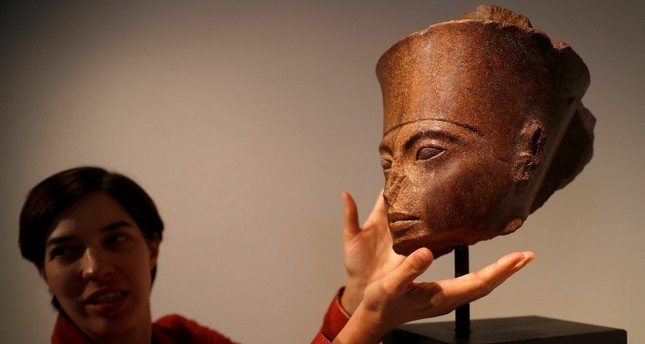 Laetitia Delaloye, head of antiquities of Christie's, poses for a photograph with an Egyptian brown quartzite head of Tutankhamun prior to its' sale at Christie's auction house in London, Britain, July 4, 2019. (Reuters Photo)