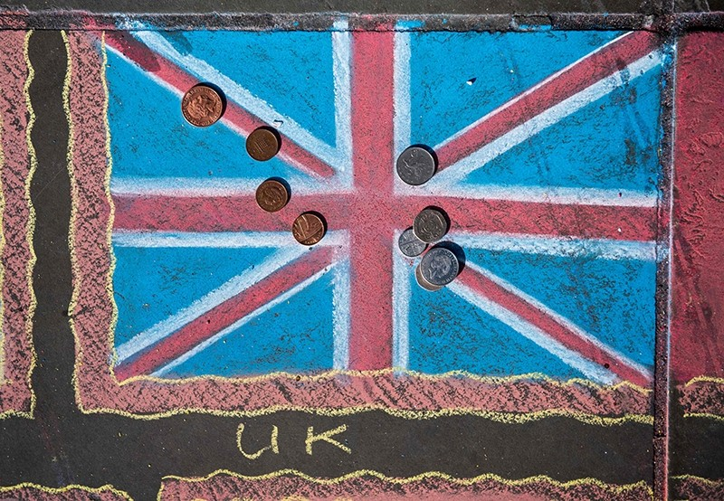 Pound coins are pictured on a chalk drawing of a Union flag on the pavement in Trafalgar Square in London on March 7, 2017. (AFP Photo)