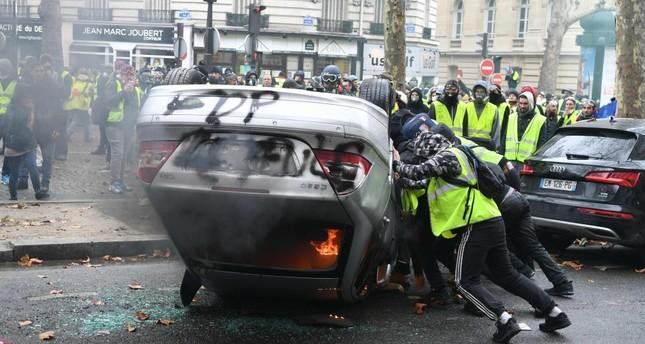 Demonstrators destroy a car during a protest on the Champs Elysees, Paris, Dec. 1.
