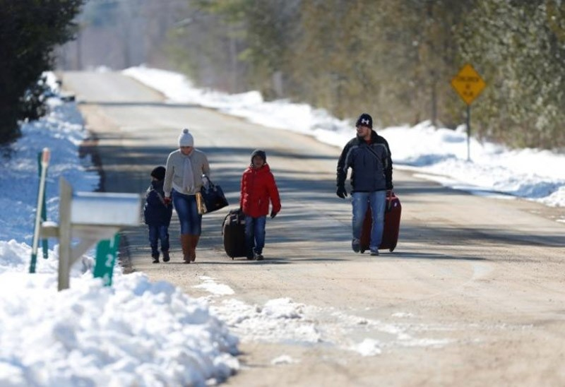A family that says they are from Colombia walks down Roxham Road toward the U.S.-Canada border leading into Hemmingford, Quebec, Canada March 26, 2017. (Reuters Photo)