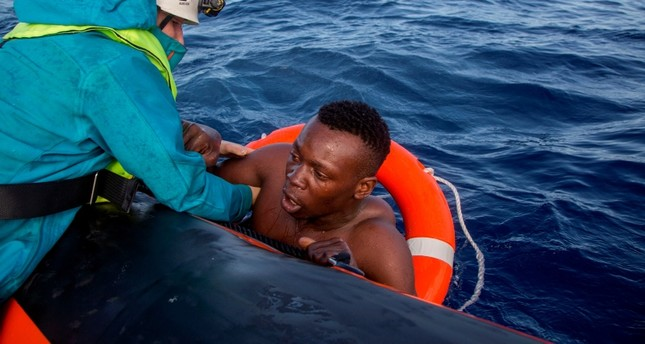 A member of German NGO Sea-Watch L helps a migrant to board a boat after he was recovered in the Mediterranean Sea on November 6, 2017. AFP Photo