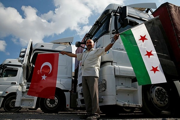 A truck driver poses for photographers in front of trucks carrying humanitarian aid destined for Idlib, Syria, by a Turkish pro-government aid group, prior to their departure in Istanbul, Monday, Sept. 10, 2018. (AP Photo)