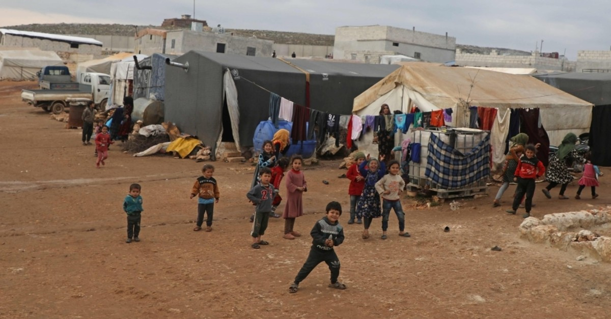 Displaced Syrian children play at an informal camp in Kafr Lusin village on the bored with Turkey in Syria's northwestern province of Idlib, on February 21, 2020. (AFP Photo)