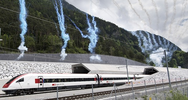 The first train comes out of the tunnel's North portal on the opening day of the Gotthard rail tunnel, at the North portal near Erstfeld, Switzerland, Wednesday, June 1, 2016. (AP Photo)