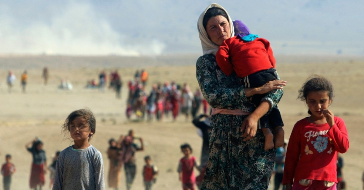 Displaced people from the minority Yazidi sect, fleeing violence from forces loyal to Daeshn Sinjar town, walk towards the Syrian border near the border town of Elierbeh of Al-Hasakah Governorate in this August 11, 2014 photo. (REUTERS Photo)