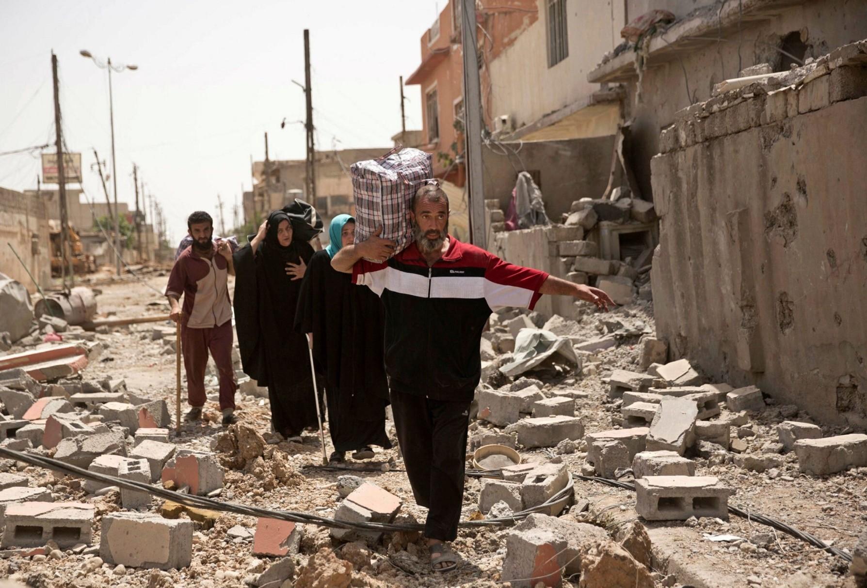 Iraqi civilians walk through the rubble of western Mosul, May 15.