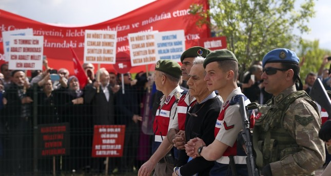 Gendarme troops accompany Akın Öztürk to the first hearing of the trial in Ankara, as families of coup victims protest him, May 22, 2017.