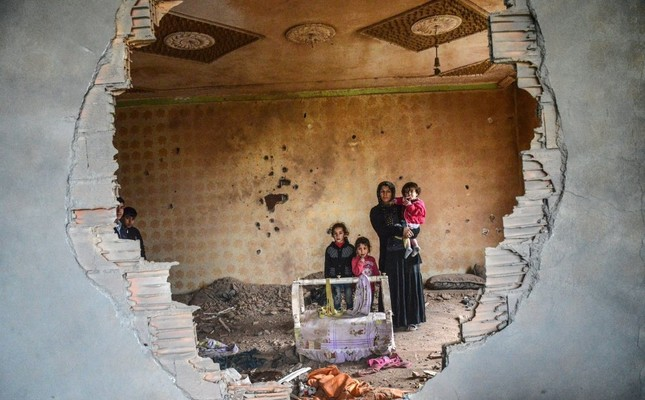 A woman and her children stand in the ruins of their house in Silopi, a town in Şırnak, in January 2016. The PKK's terror campaign left many displaced last year.